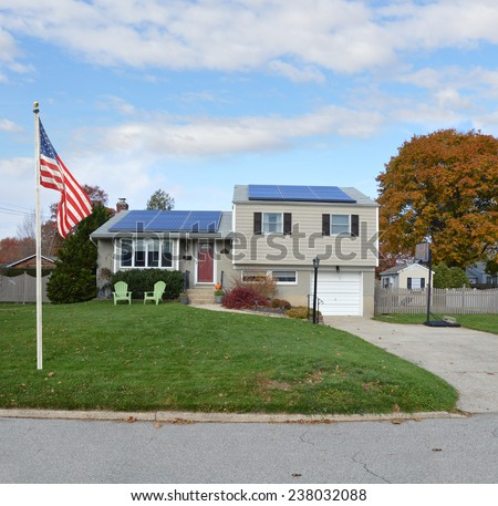 American flag pole Suburban high ranch house autumn day residential neighborhood blue sky clouds USA - stock photo