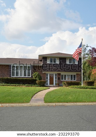 American Flag pole Suburban home cement walkway front yard lawn residential neighborhood blue sky clouds USA