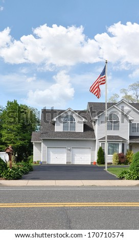 American Flag Pole Suburban Home Driveway Two Car Garage Residential Neighborhood Street USA blue sky clouds - stock photo