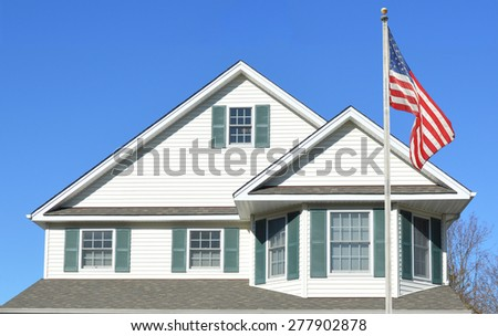 American Flag pole Suburban Home Roof Windows Sunny clear blue sky day residential neighborhood USA - stock photo