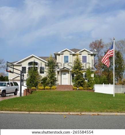 American flag pole Suburban McMansion Home Sunny Residential Neighborhood USA Blue Sky clouds - stock photo