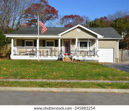 American flag pole Suburban Ranch style home with porch sunny autumn day residential neighborhood clear blue sky USA - stock photo
