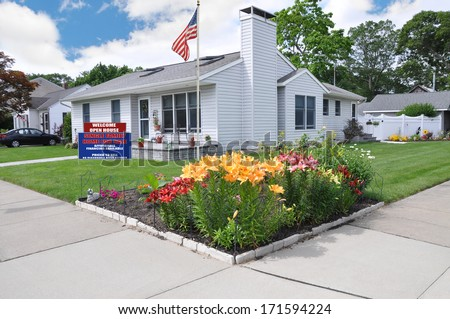 American Flag Pole Tulips Landscaped Front Yard For Sale Real Estate Sign USA residential neighborhood Suburban Home Blue Sky clouds - stock photo