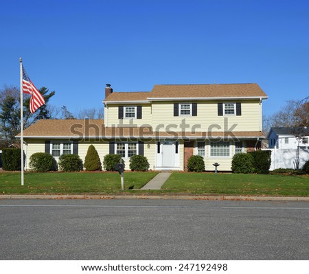 American flag pole Yellow McMansion style home clear blue sky autumn day residential neighborhood USA