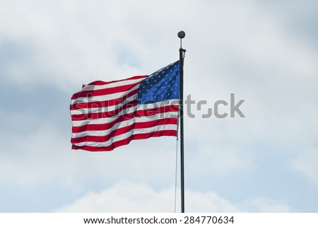 American flag proudly on display during a cloudy day.