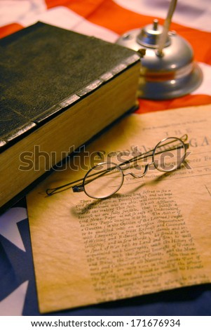 American flag, quill pen, bible, and antique news paper from the Founding Fathers. - stock photo