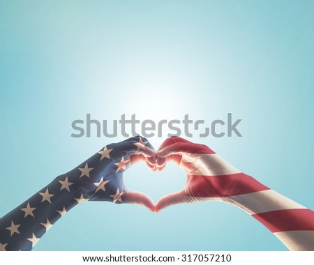 American flag red white blue star pattern on people hands in heart love shape on blue vintage color background: USA patriot, veterans, independence day, constitution and citizenship day concept  - stock photo