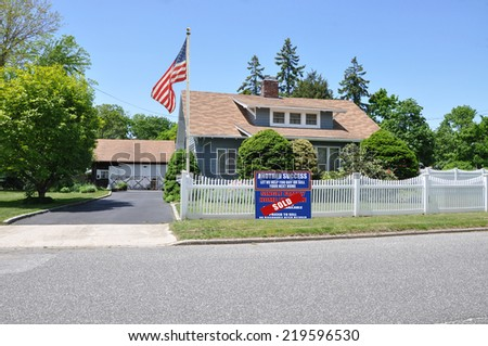 American Flag Sold (Another success let us help you buy sell your next home) real estate sign on front yard lawn of suburban home with white picket fence clear blue sky USA residential neighborhood - stock photo