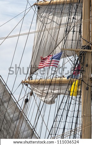 American Flag Surrounded by Rigging and Sails of a Tall Ship - stock photo