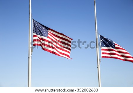 American flag swaying on the pole on the bright blue sky