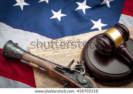 American flag, US constitution, a gavel and  and musket type pistol, which was the type of handgun used at the time of the signing of the constitution - stock photo