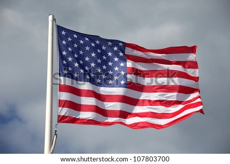 American flag waving against a cloudy sky - stock photo
