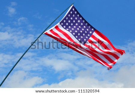 American flag waving against blue sky.