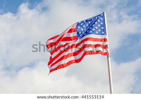 American flag waving against cloudy blue sky, focus on star of waving flag.
