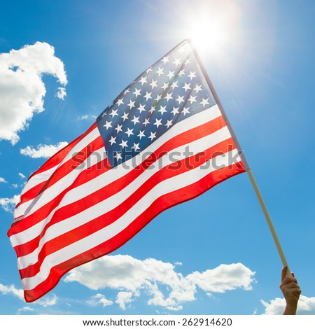 American flag waving in blue sky with sun behind it - stock photo