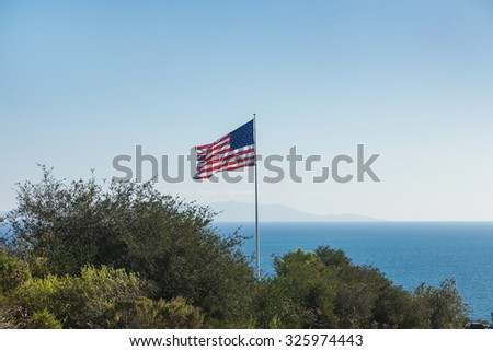 American flag waving in the breeze with a background of blue ocean, and the shore covered with green trees