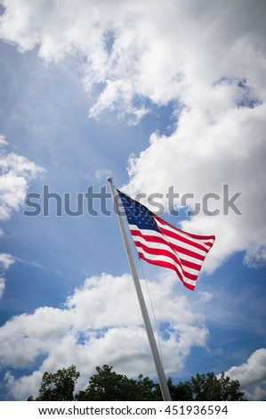 American flag waving in the sky on a windy summer day