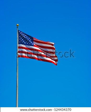 American flag waving in the wind against a blue sky ina sunny day - stock photo