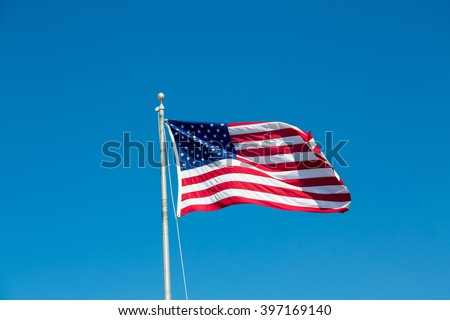 American flag waving in the wind on a blue sky - stock photo