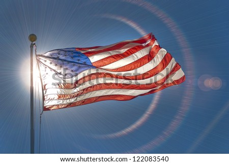 American flag waving in the wind with lens flare - stock photo