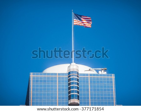American flag waving on top of a modern skyscraper high in the air on a sunny day against the blue sky - stock photo