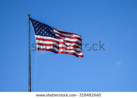 American flag waving with clear blue sky. - stock photo