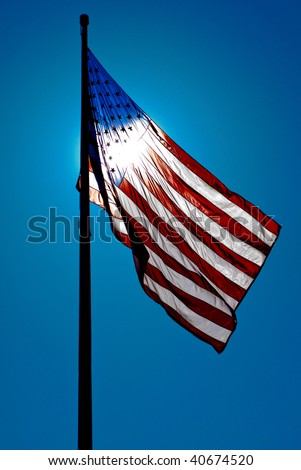 american flag with the sun shining through the flag - stock photo