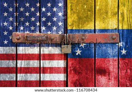 American flag with the Venezuelan flag on the background of old locked doors - stock photo