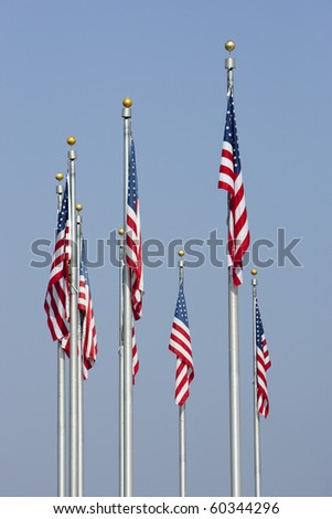 American Flags against blue sky in vertical orientation. Focus on middle front flag.