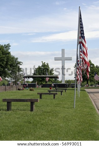 American flags lining cemetery street with huge cross in background. - stock photo