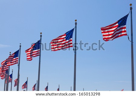 American flags - star and stripes floating over a cloudy blue sky