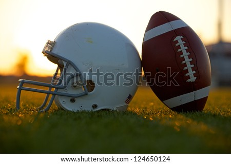 American Football and Helmet on the Field Backlit at Sunset - stock photo