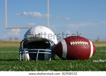 American Football and Helmet on the Field with Goal Posts in the background - stock photo