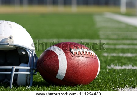 American Football and Helmet on the Field with room for copy - stock photo