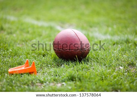American football ball with football kicking tee - stock photo