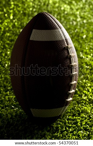 American football close up at night on flood lit green field (dark mood) in kicking position - stock photo