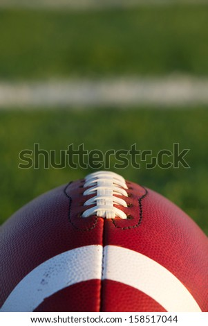 American Football Close Up with the Field Beyond - stock photo