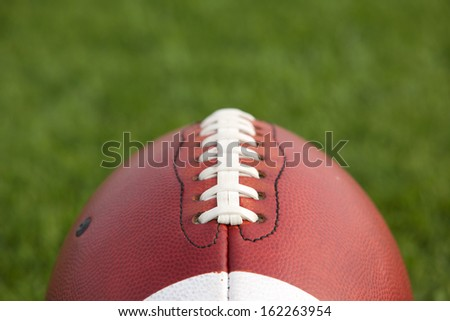 American Football Close Up with the Turf beyond for Copy Space - stock photo