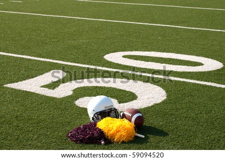 American football, helmet, and pom poms on field next to 50 yard line. - stock photo