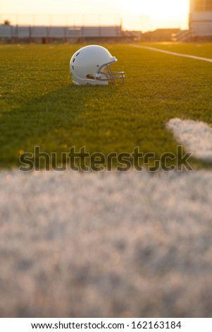 American Football Helmet Backlit on the Field at Sunset with room for copy - stock photo
