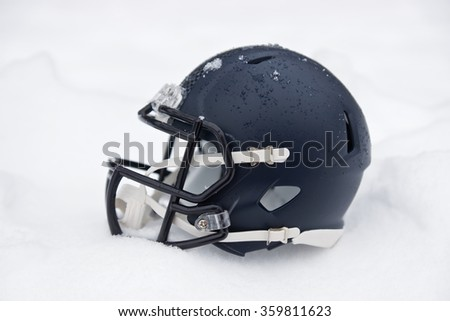 american football helmet covered in the snow and ice