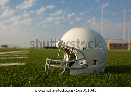 American Football Helmet on the Field with Goal Posts Beyond - stock photo