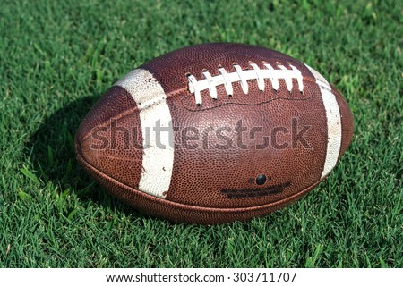 American football in center of frame sitting on grass