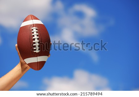 American Football in Hand over Blue Sky - stock photo
