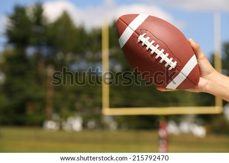 American Football in Hand over Field with Goal Post or Uprights  - stock photo