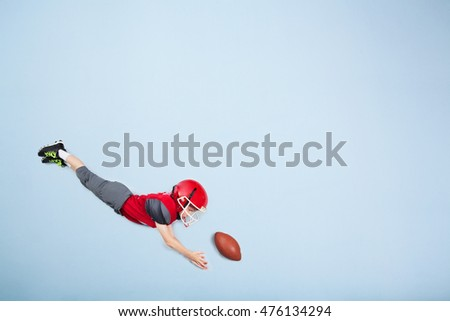 American football kid wearing full pads and helmet is diving for the catch. Blue background with copy space