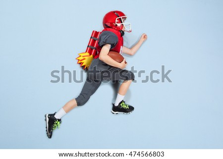 American football kid wearing full pads and helmet is running the ball with rocket boosters on his back.  Blue background