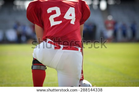 american football kneeling on stadium, out of focus players in the background - stock photo