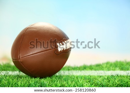 American football on field on green grass, on blue sky background - stock photo