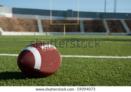 American football on field with goal post in background. - stock photo
